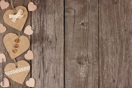 Fotografía  Side border of handmade burlap hearts with ribbon and buttons over a rustic wood