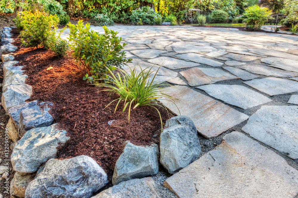 Fototapety, obrazy: Completed flower beds around new stone patio with plants in place