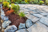 Fototapeta Kamienie - Completed flower beds around new stone patio with plants in place