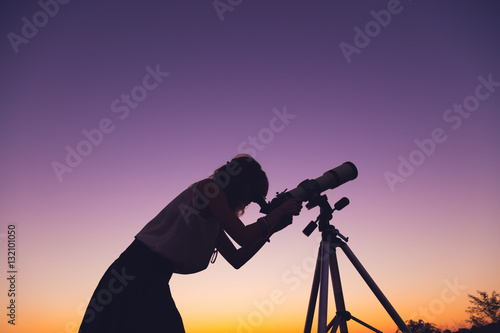Fotomural Girl looking at the stars with telescope beside her.