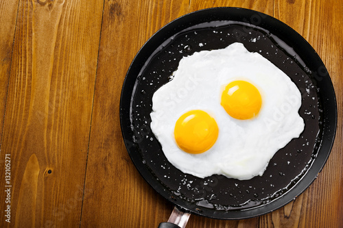 Foto op Plexiglas Gebakken Eieren Delicious healthy simple breakfast meal made of eggs on a frying pan ready. Traditional homemade quick breakfast. International cuisine food. Top view.