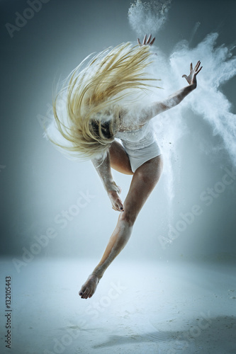 Fotografia  Woman dancer in high jump with flour in studio white background
