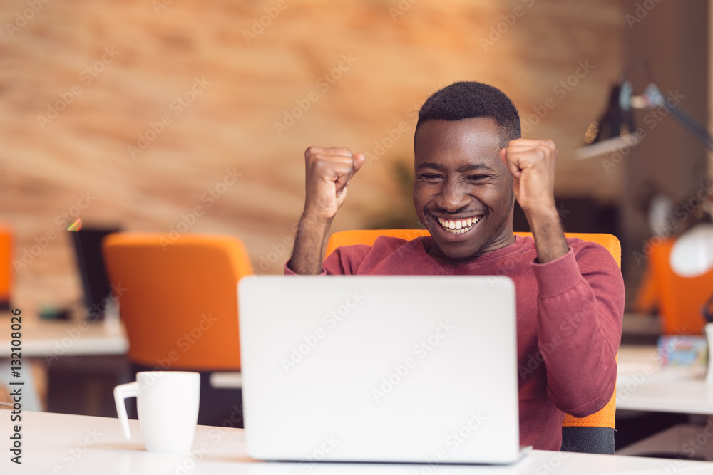 Fototapeta Happy successful African American businessman in a modern startup office indoors