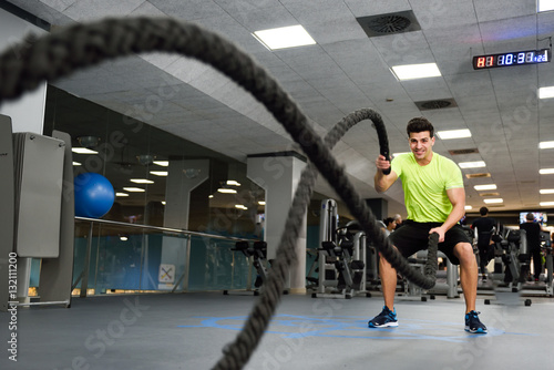 Fotografía  Man with battle ropes exercise in the fitness gym.