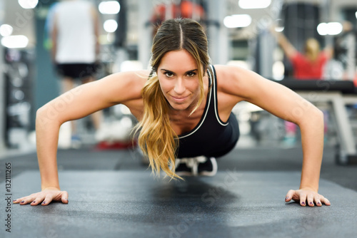 Deurstickers Fitness Young beautiful woman doin pushups in the gym.