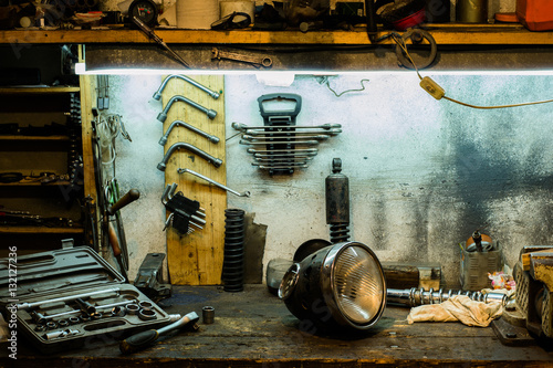 Fotografie, Obraz  Motorcycle parts on the desktop in the garage