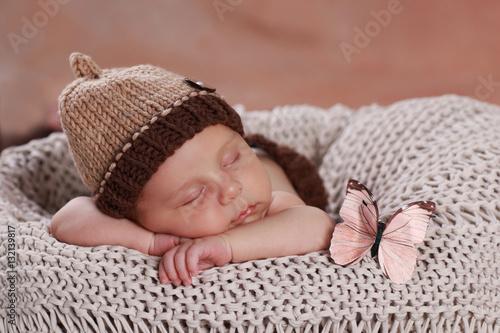 spiace-dziecko-w-czapce-i-z-rozowym-motylkiem