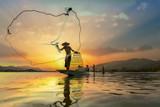 Azjatyccy rybacy na łódkowatym połowie przy jeziorem - 132143483