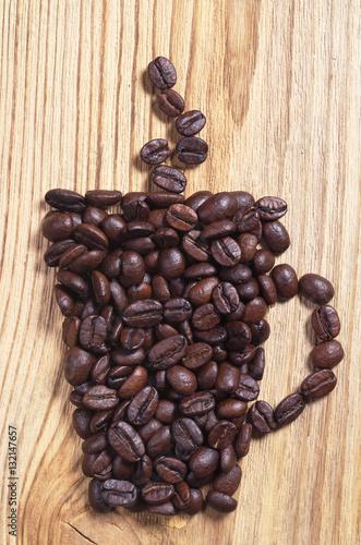 kubek-kawy-ulozony-z-ziaren-na-drewnianym-tle