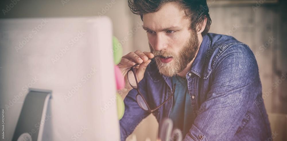 Fototapeta Focused hipster working at his desk