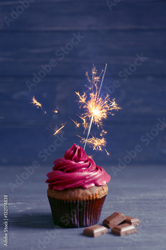 Photo  Tasty cupcake with sparkler and chocolate on wooden table against dark backgroun