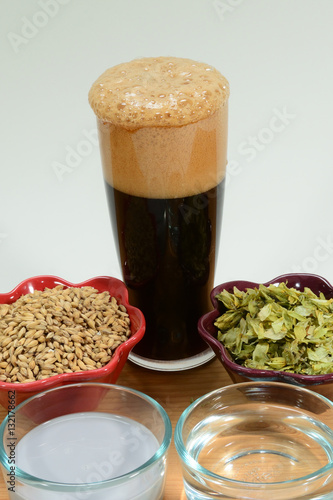 Fotografia, Obraz  Home Brew Beer ingredients shown with a glass of foamy beer with malted barley g