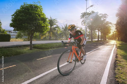 Man riding bicycle on the tiled road in the park  - Buy this stock