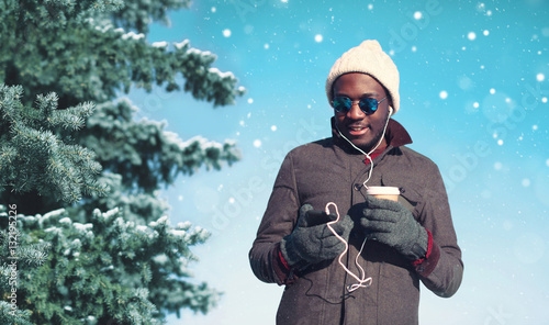 Stickers pour porte Magasin de musique Winter young smiling african man enjoying listening music on sma