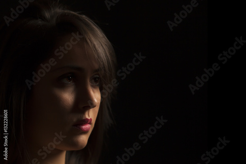 Tuinposter Boeddha Thoughtful low key portrait of beautiful young woman. Black background