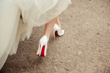 Beautiful Bride's Shoes With Long Legs In White Wedding Dress