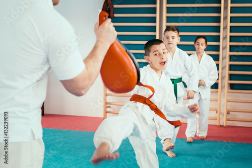 Photo Stands Martial arts Tae kwon do training. Group of children on Tae kwon do training