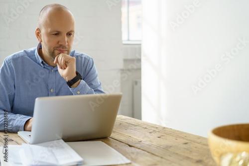 Fotomural  nachdenklicher mann schaut auf seinen laptop