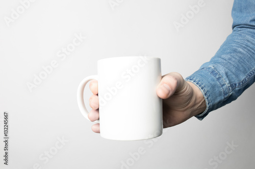 Hand in blue shirt is holding white coffee cup