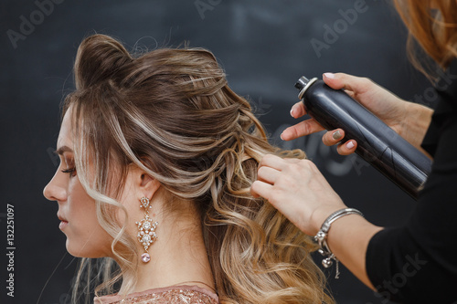 Fotografie, Obraz  Hairdresser using hairspray on client's hair at salon