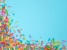 Border Frame Of Colorful Sprinkles On Blue Background