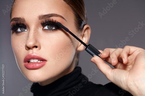 Valokuva  Beauty. Beautiful Woman Applying Black Mascara On Eyelashes