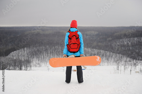 Poster Wintersporten The girl with a snowboard standing on her back on top of a monochrome background of a winter landscape