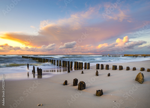 Aluminium Prints Dark grey beach and offshore breakwaters during a beautiful sunset, baltic sea