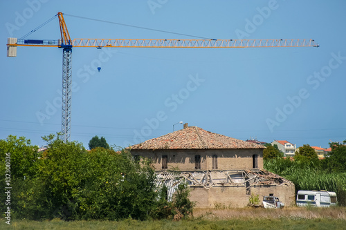 Photo  Landscape with a dilapidated house and the tower crane