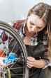 Attentive young craftswoman fixing the wheel of the bicycle