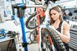 Watchful female worker repairing bicycle in the garage
