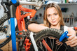 Attractive female technician repairing the bicycle in the garage
