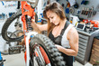 Persevering female master repairing the mountain bicycle