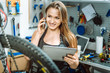 Delighted young mechanic using devices in the repair shop