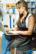 Concentrated female mechanic surfing the Internet in the workshop