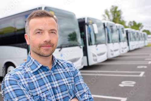 posing with a row of buses