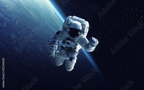 Astronaut at spacewalk. Cosmic art, science fiction wallpaper. Beauty of deep space. Billions of galaxies in the universe. Elements of this image furnished by NASA - 132366202