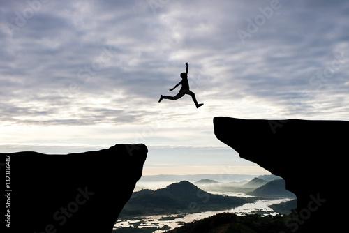 Obraz na plátně Man jump through the gap between hill