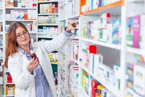 Foto op Canvas Apotheek Woman pharmacist holding prescription checking medicine in pharmacy (or drugstore