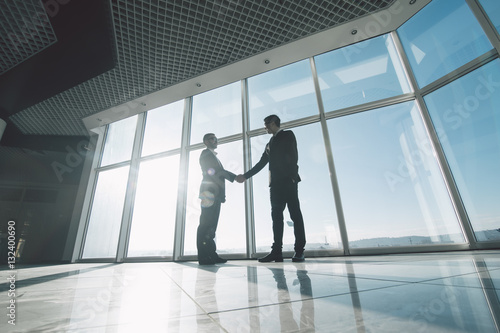 Two young businessmen are shaking hands with each other standing against panoramic windows Wallpaper Mural