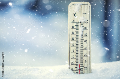 Obraz Thermometer on snow shows low temperatures under zero. Low temperatures in degrees Celsius and fahrenheit. Cold winter weather twenty under zero. - fototapety do salonu