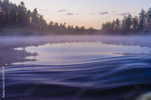 Summer landscape with river, forest, clouds on the blue sky and sunset.