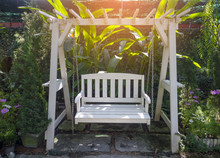 White Wooden Porch Swing In Ga...