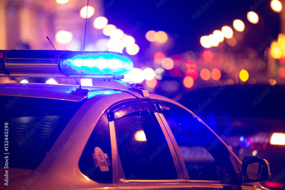 Fototapeta Blue light flasher atop of a police car. City lights on the background.