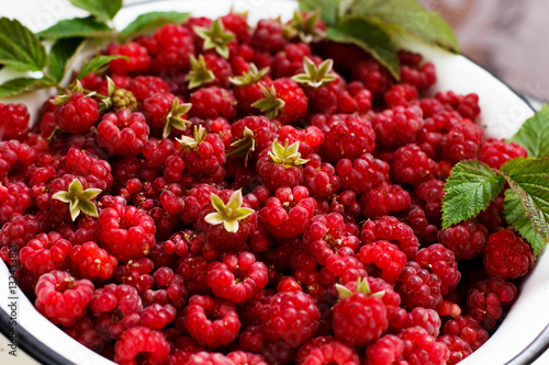 Juicy flavour organic maroon raspberry with grean leaves in white bowl - 132453813