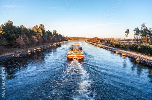 Fotografia  inland vessel drives a canal river along