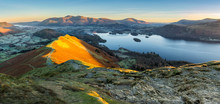 Panoramic View Of Derwentwater In The Lake District With Warm Morning Light Illuminating Catbells.