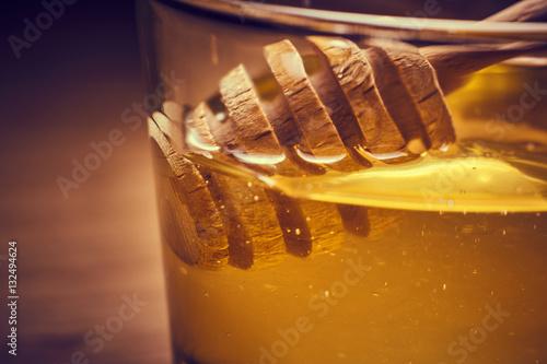 Valokuva  Tazza in vetro, con miele e cucchiaio in legno,