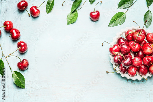 Obraz Red ripe cherry  berries in bowl with twigs and leaves on light blue background, top view frame. Summer berries concept - fototapety do salonu