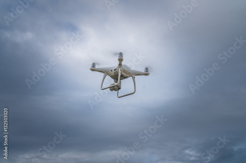 Flying drone with cloudy sky background controlled by